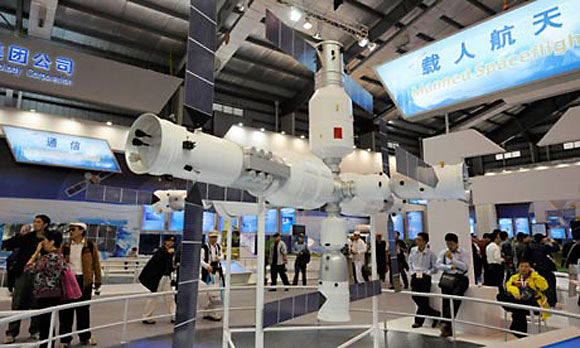 Visitors to the Airshow China exhibition look at a model of the Tiangong-1 space station