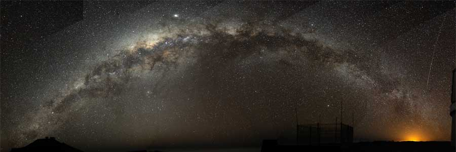 A fish-eye mosaic of the Milky Way arching at a high inclination across the night sky, shot from a dark-sky location in Chile