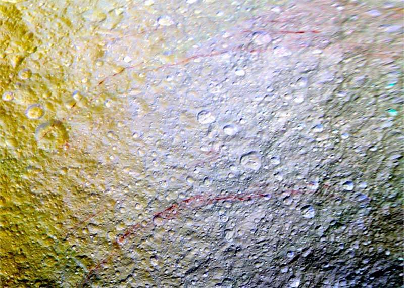 Unusual arc-shaped, reddish streaks cut across the surface of Saturn's ice-rich moon Tethys in this enhanced-color mosaic.