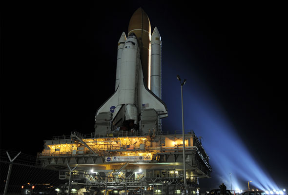 Bathed in bright xenon lights, space shuttle Discovery